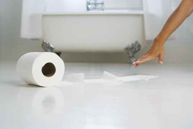 Woman Reaching for Toilet Paper Roll on the Floor