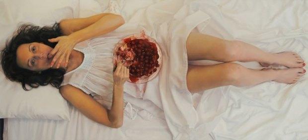 La artista Lee Price se autoretrata comiendo una tarta con cerezas en la cama