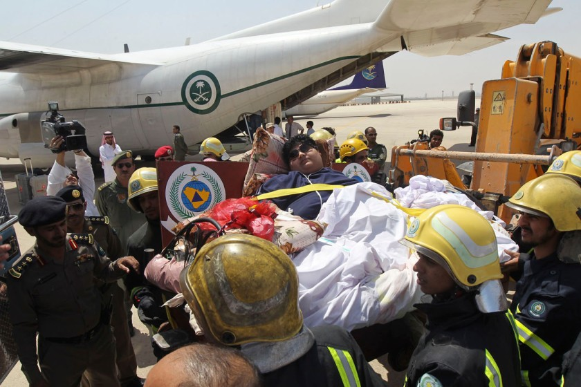 Saudi Civil Defence members move Shaeri onto a plane to airlift him to Riyadh for medical treatment, in Jizan