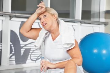 Mujer en meopausia sudando en el gym