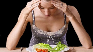 Young woman looking at plate of salad  GETTY